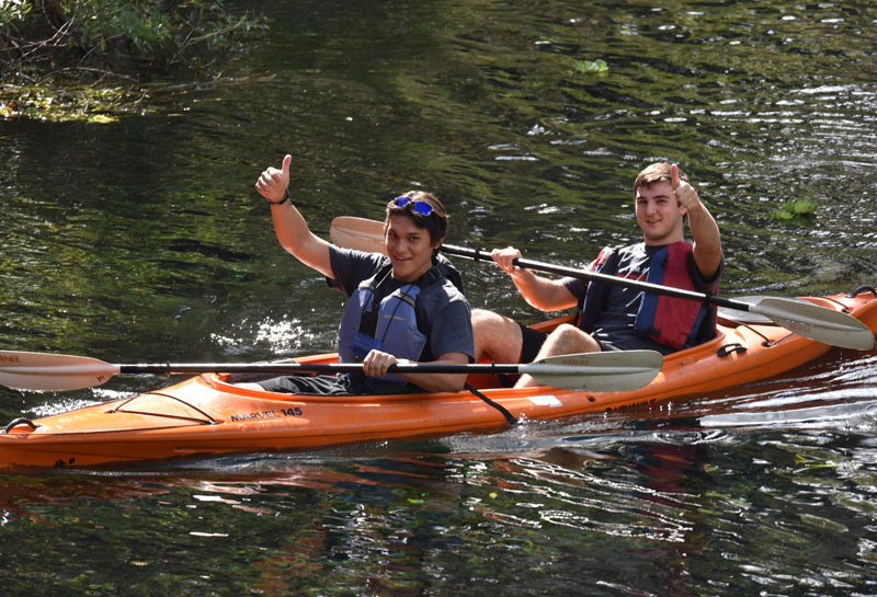 Student kayaking and giving thumbs up